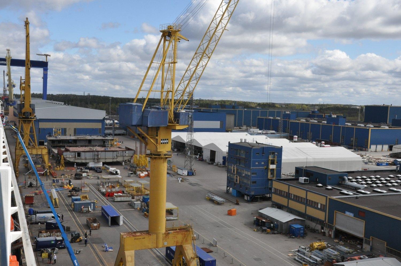 Vy över varvsområdets produktionshallar vid varvet Meyer Turku i Åbo. I förgrunden står en lyfdtkran. lyfkranhft
