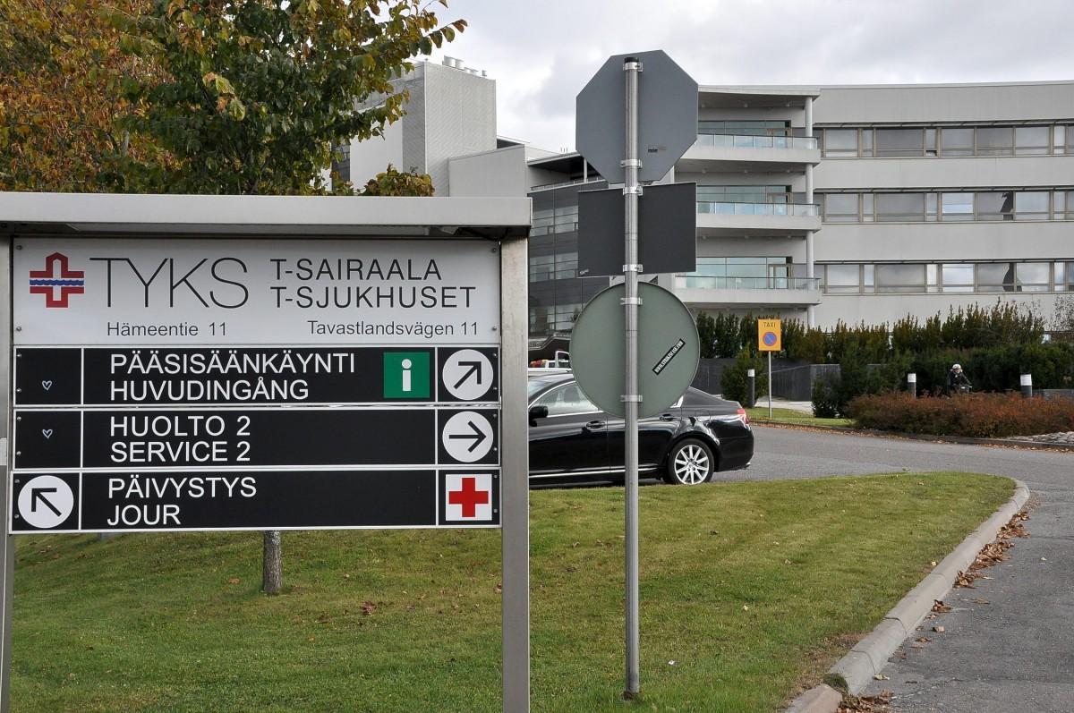 Skyltar med sjukhusbyggnad i bakgrunden.