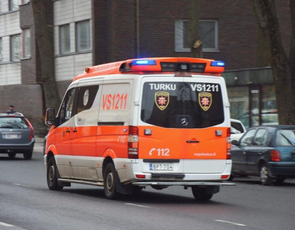 En ambulans kör med blåljusen påslagna.