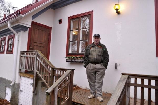 En man står på en trappa framför ett vitt hus.