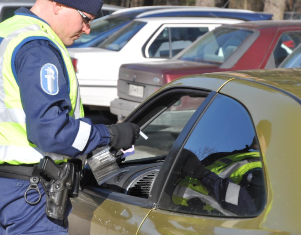 En polis gör blåstest på en bilist som sitter i bilen