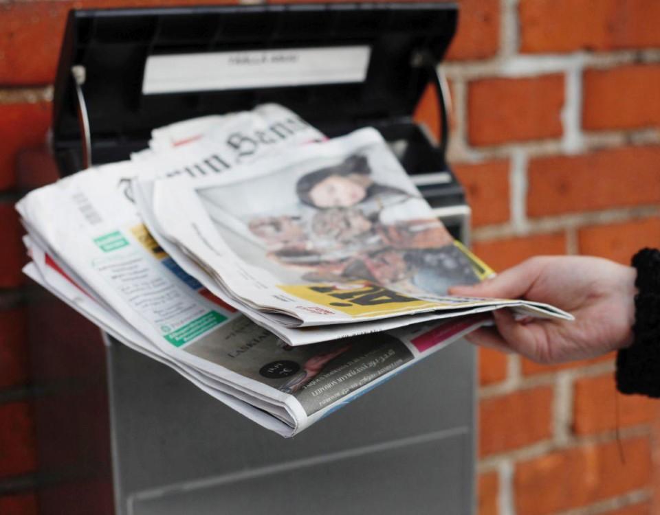 En hand med en bunt tidningar framför en postlåda.