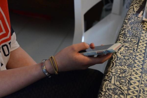 En ung person håller en smarttelefon i handen