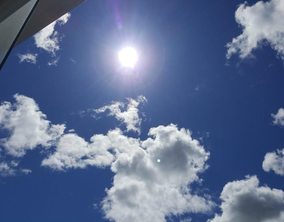 Sol på en blå himmel med några små moln.
