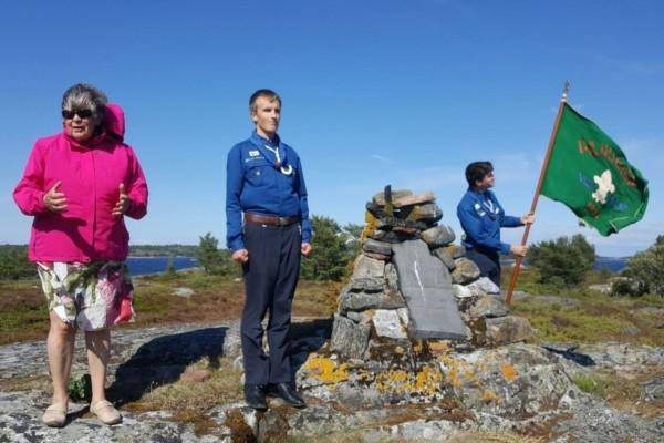 Kvinna och två ynglingar står vid monument på klippa