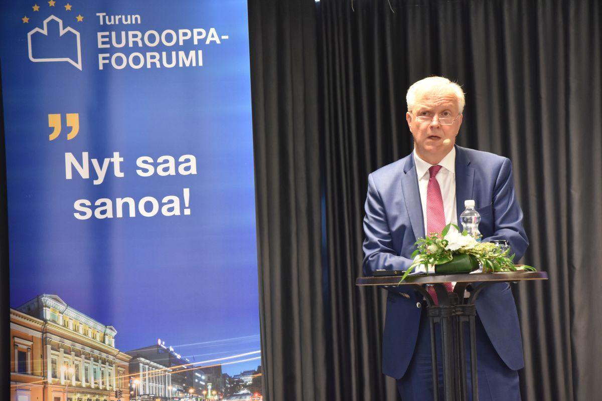Olli Rehn står på en scen och talar.