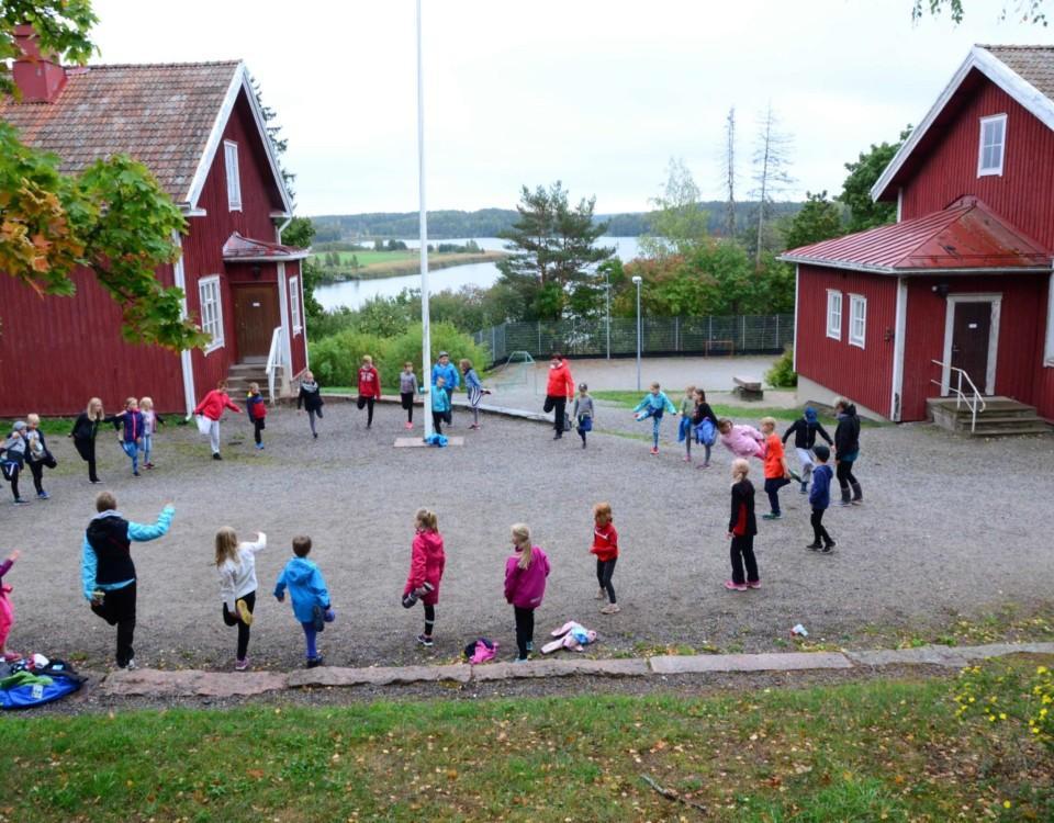 röda trähus och gård där barn leker