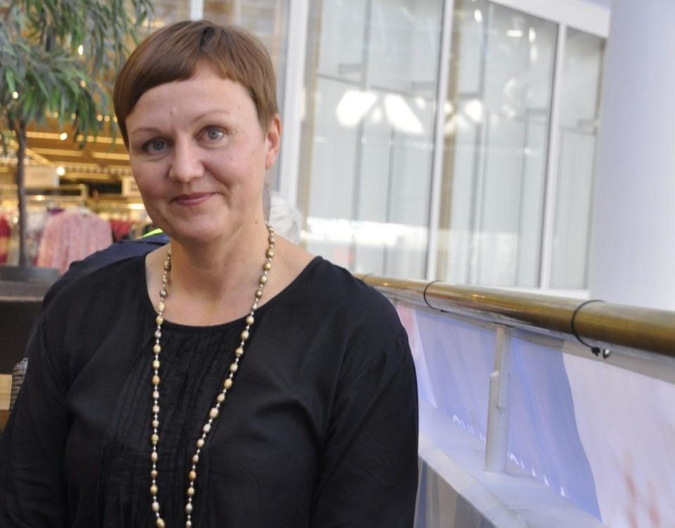 Kvinna med långt halsband och svart skjorta.