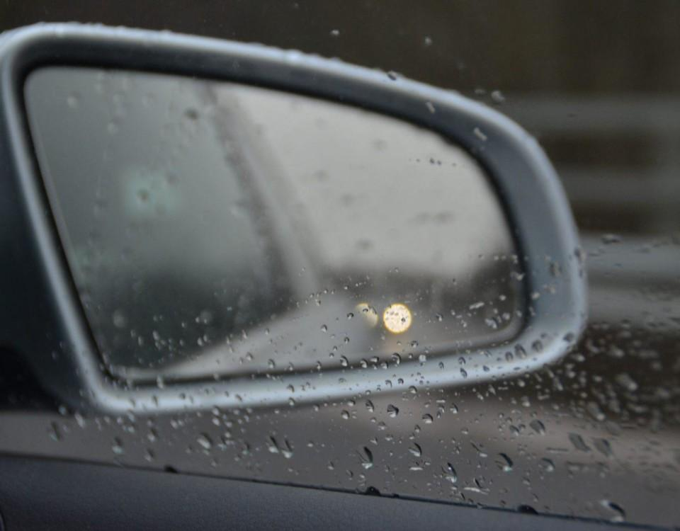 En backspegel med regndroppar.