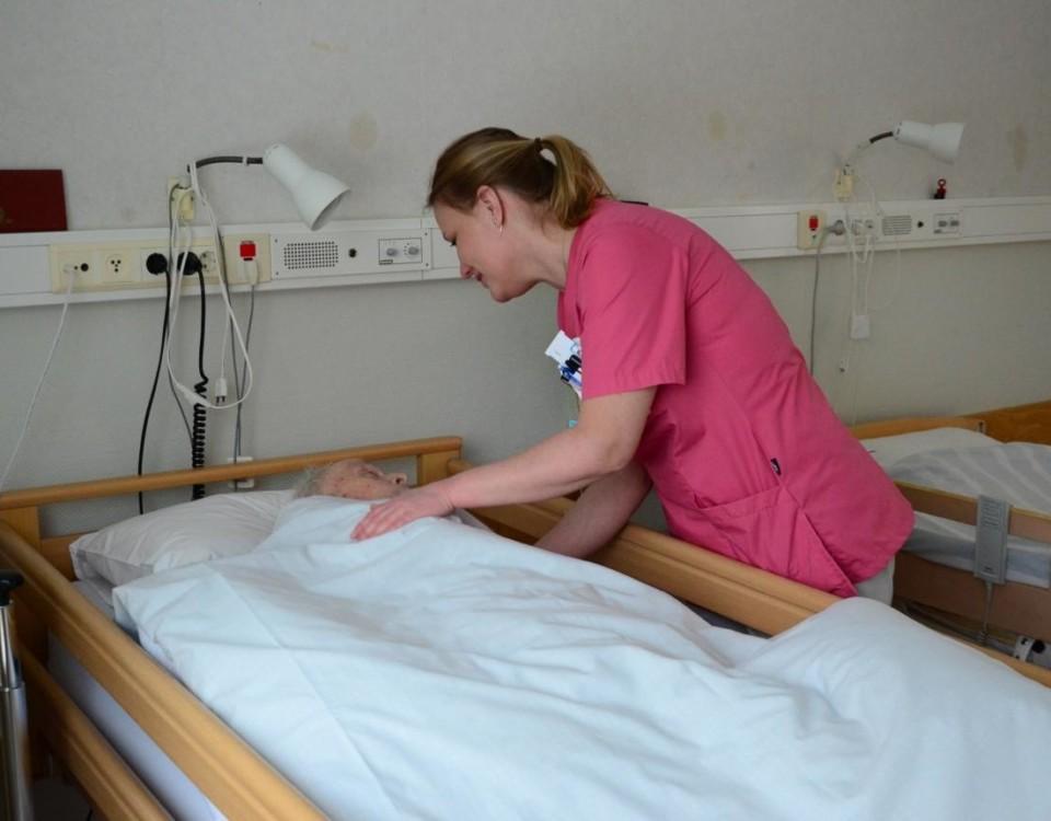 Sköterska böjer sig ner och talar med en patient