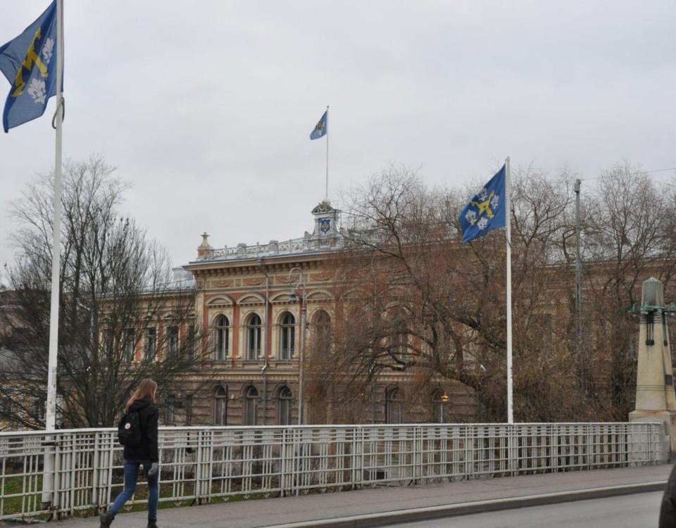 Stadshuset i Åbo med Aura bron och flaggstångar med stadens flagga hissade i förgrunden.