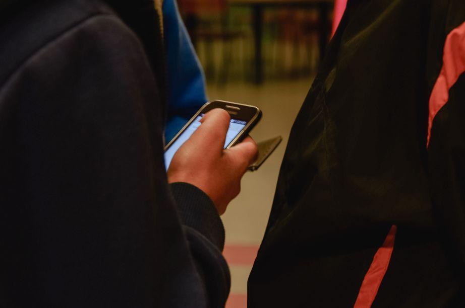 Hand som håller i en telefon.