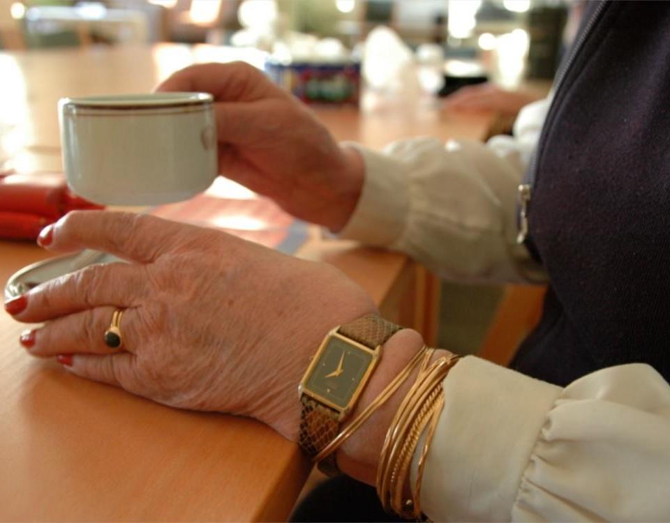 En äldre persons händer som håller i en kaffekopp.