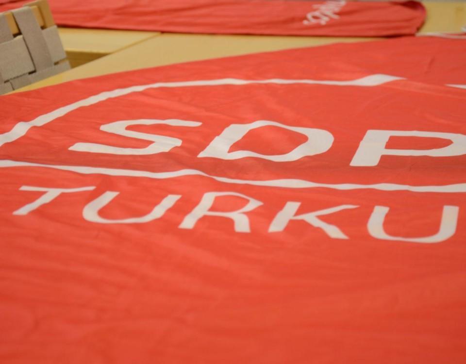 """Röd skylt med texten """"SDP Turku"""" ligger på ett bord."""