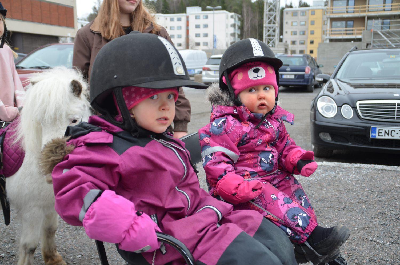 Två små flickor med en häst bakom sig.