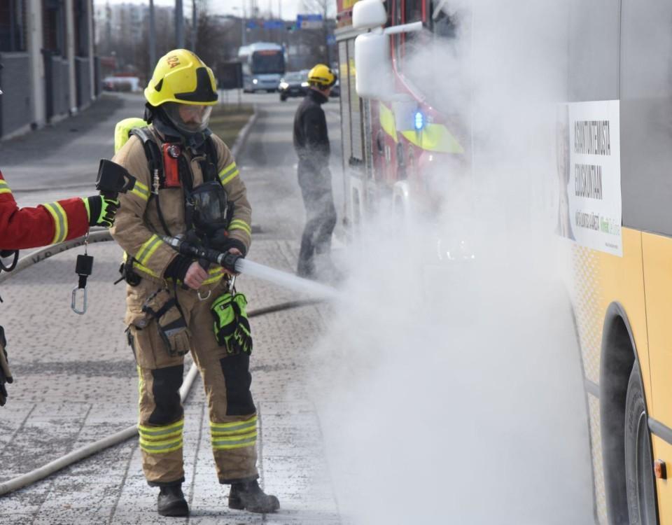Brandman släcker brinnande buss.