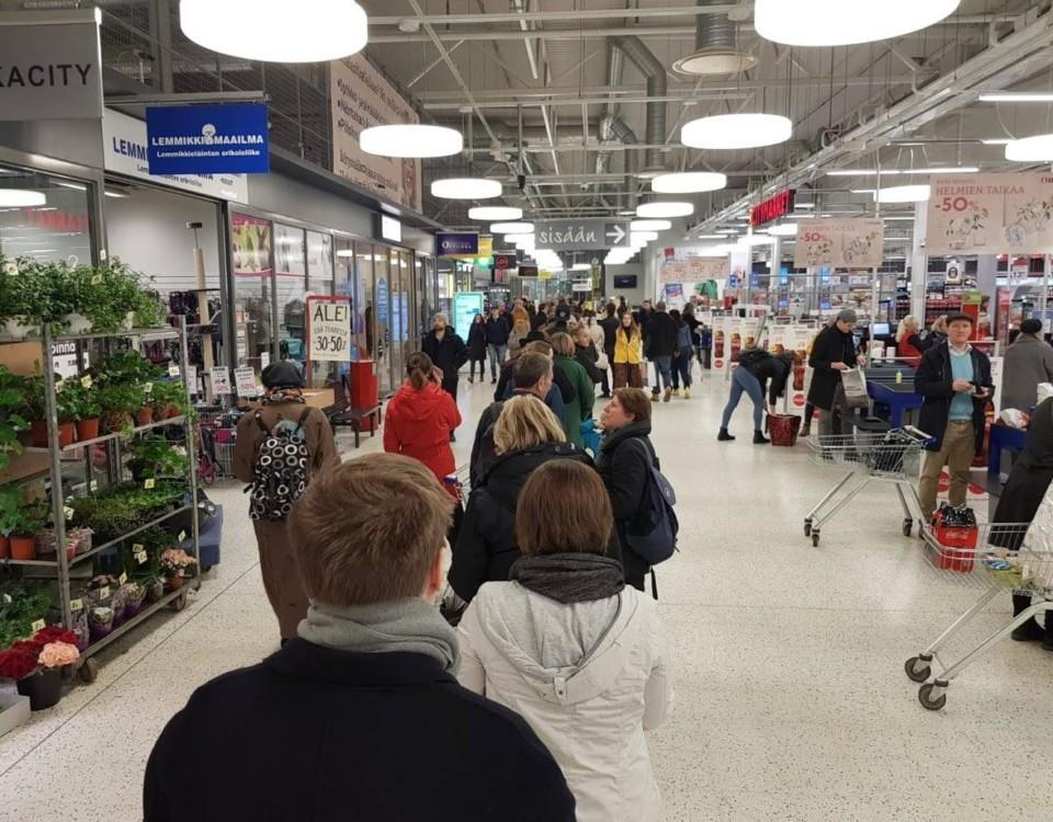 Människor som köar inomhus i en storhandel.