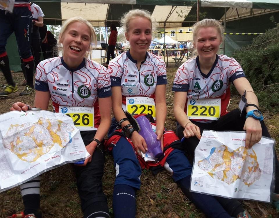 Tre glada kvinnor i sportkläder, med kartor i händerna