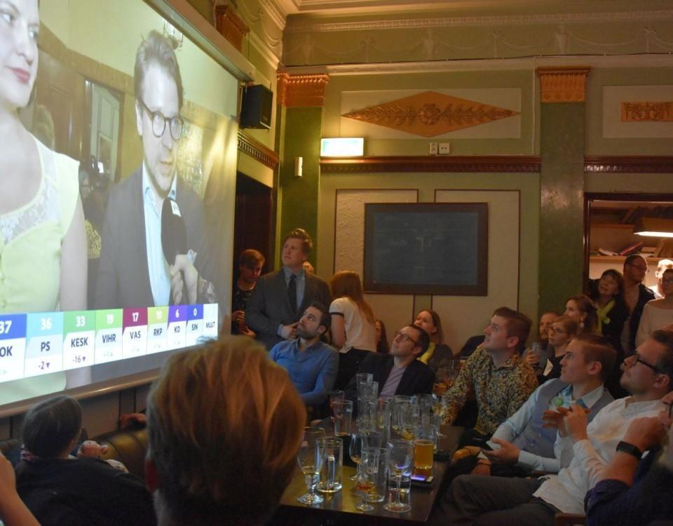 Fullsatt barsal med många människor som tittar på en stor skärm med tv-program.