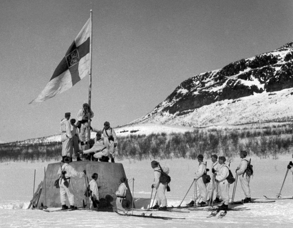 Soldater reser flaggan vid treriksröset