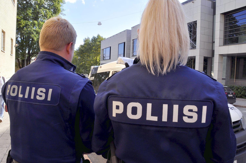 Två poliser i uniform står med ryggen åt kameran.