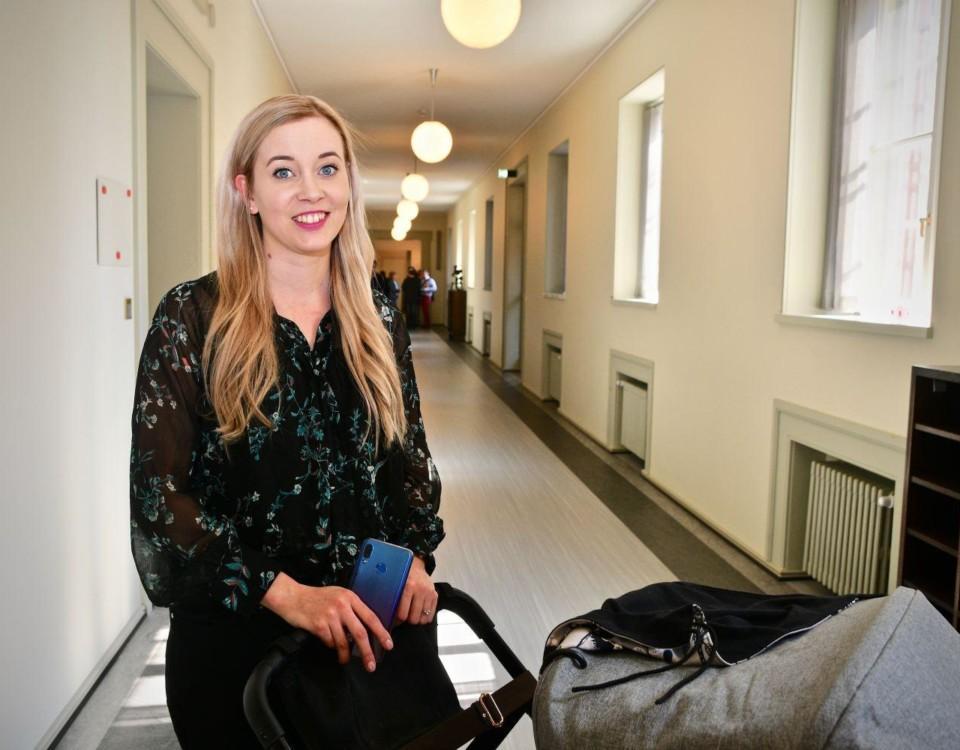 Kvinna med barnvagn i en korridor.