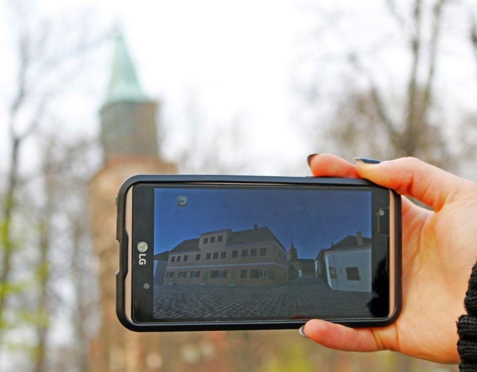 Mobiltelefon håls upp, kyrka i bakgrunden