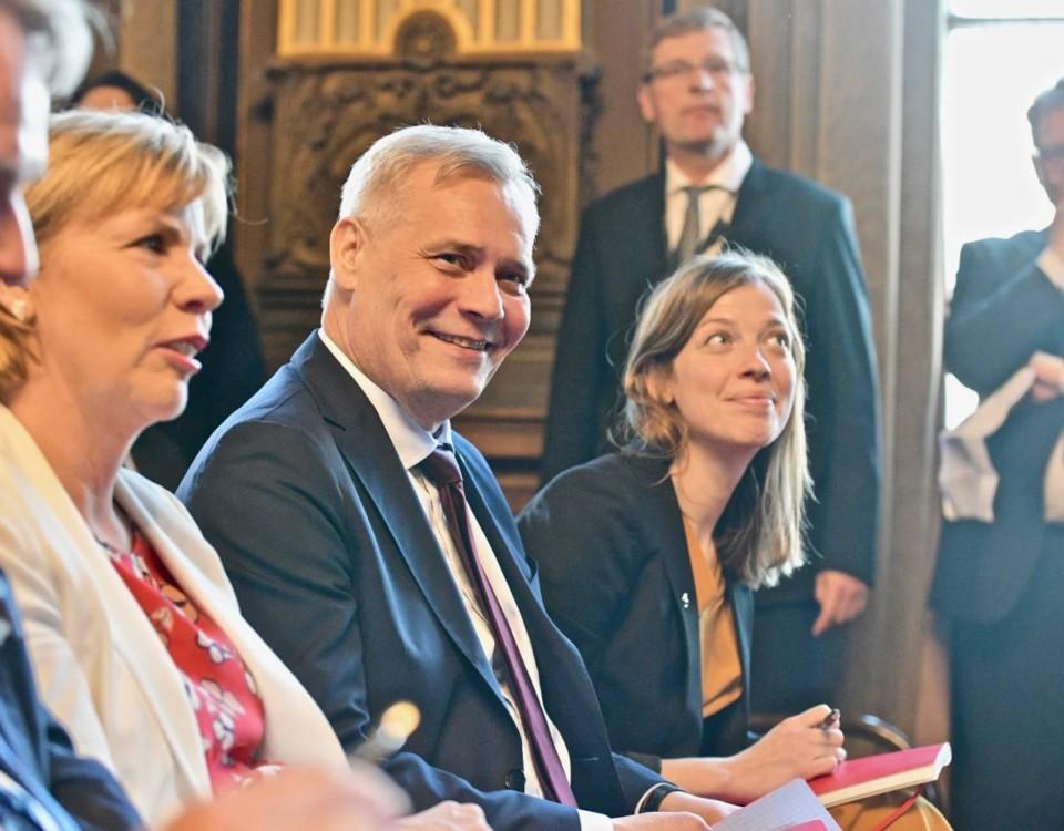 Två leende kvinnor och en man.