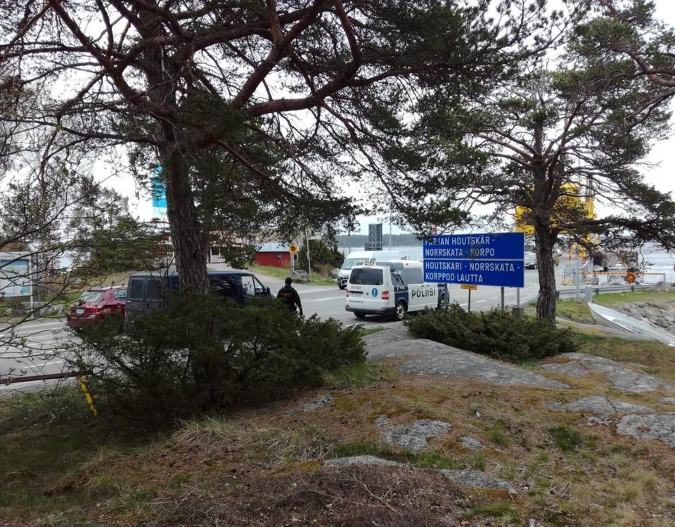 En polisbil och en blå skåpbil vid färjefästet.