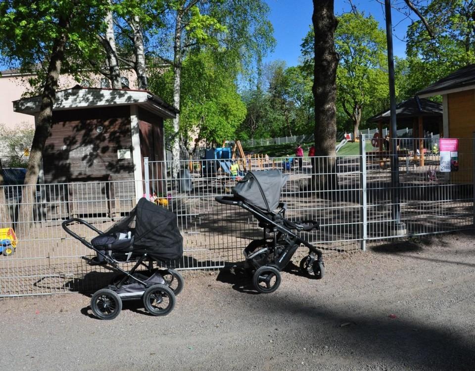 Två barnvagnar står parkerade utanför en inhägnad lekpark.