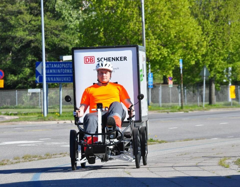 En person sitter på en stor elcykel med fyra hjul och en låda bakom.