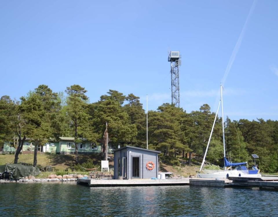 En lugn vik med en brygga, en segelbåt och en bastu på en flotte. I bakgrunden ett vakttorn.