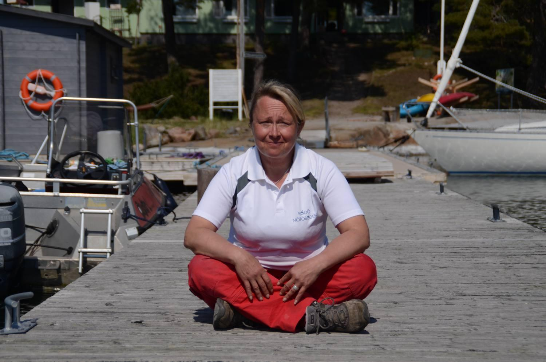 Kvinna med röda byxor som sitter på en brygga.