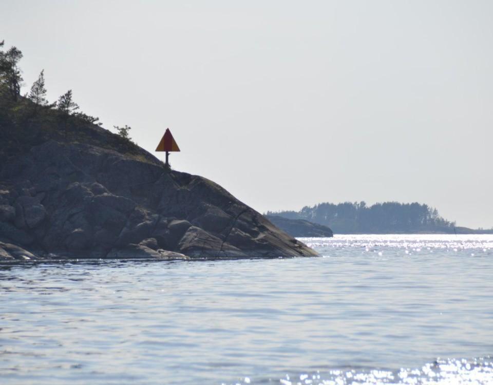Glittrande hav och en klippa med ett sjömärke på.