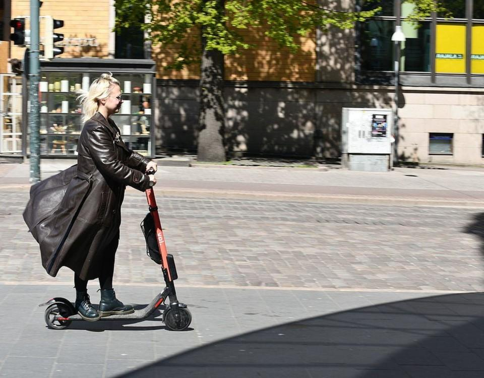 Kvinna åker elsparkcykel.
