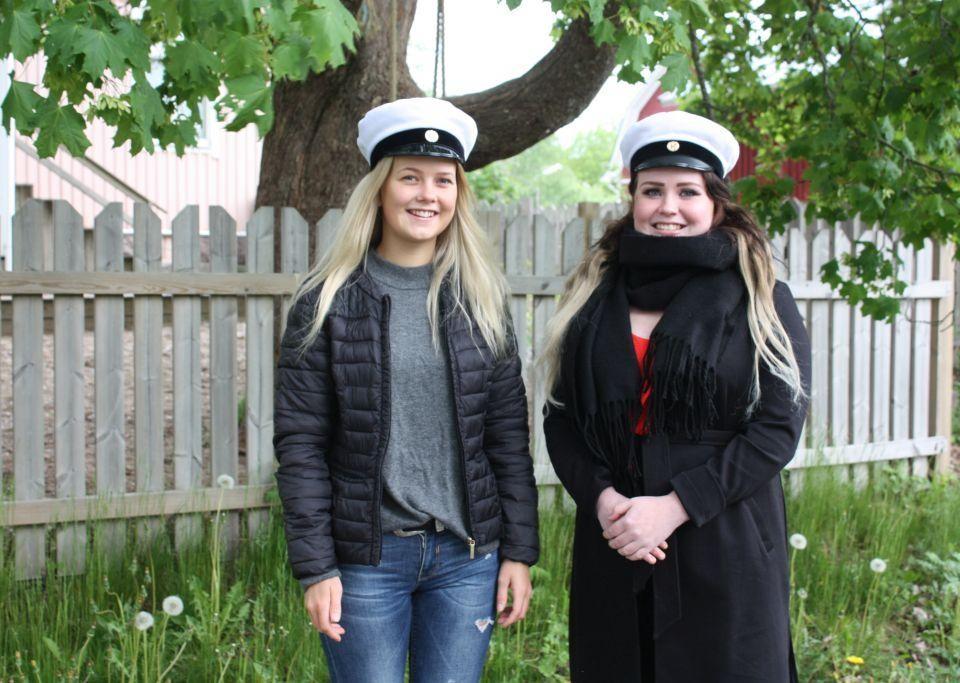 Melinda Johansson och Emilia Jansson, utomhus, ler och tittar in i kameran, med studentmössor på huvudet, i bakgrunden ett vitt staket, grönt lövträd och rött hus