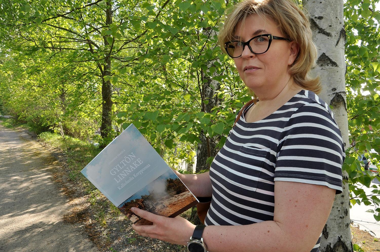 Kvinna med bok i handen , i bakgrunden grönskande träd