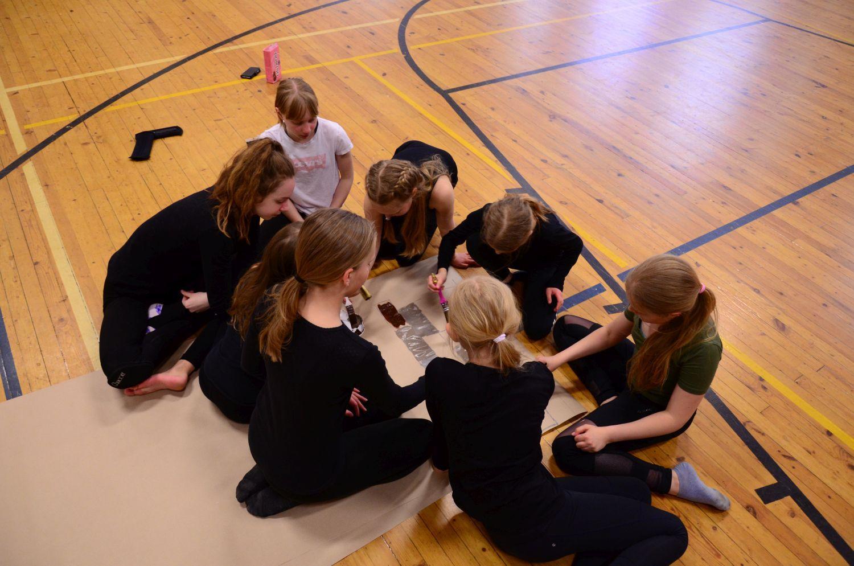 Medlemmarna i gymnastikgruppen Aurora pysslar ihop kulisser för vårfesten.