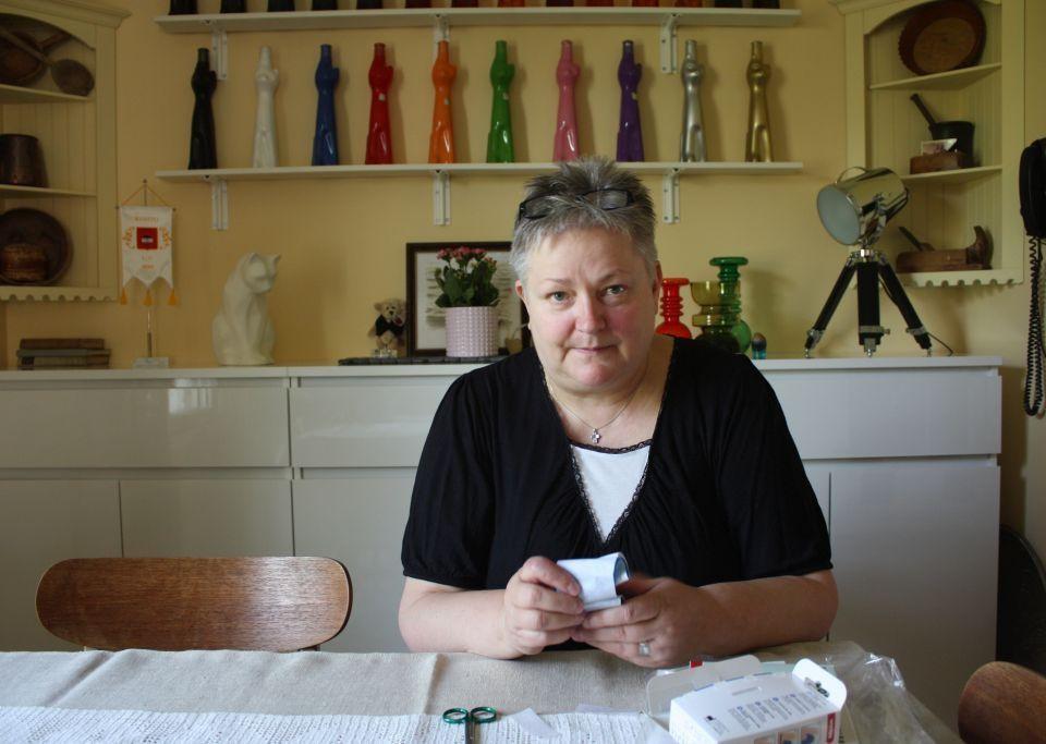 Mona Söderblom sitter vid ett bord och håller en plsterförpackning i handen, i bakgrunden en vit byrå och inredningsprydnader