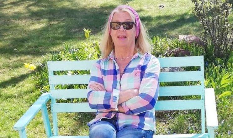 En kvinna sitter på en bänk ute i solen.