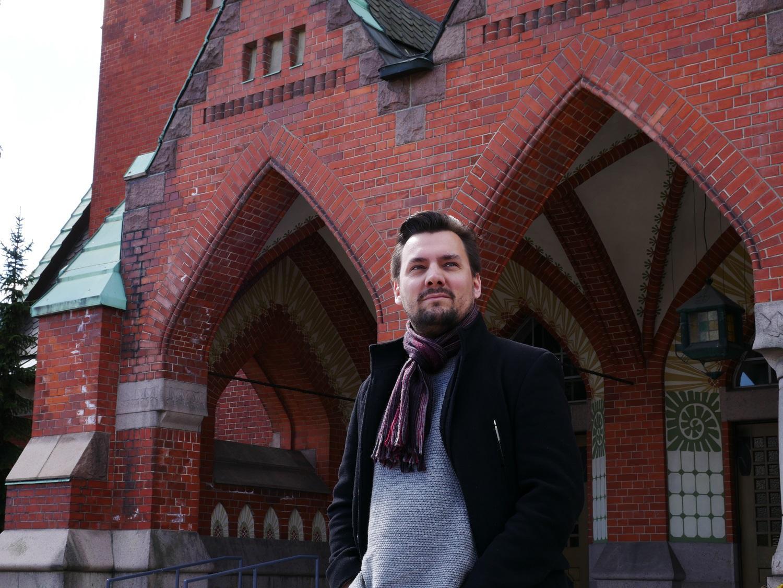En man står framför en kyrka