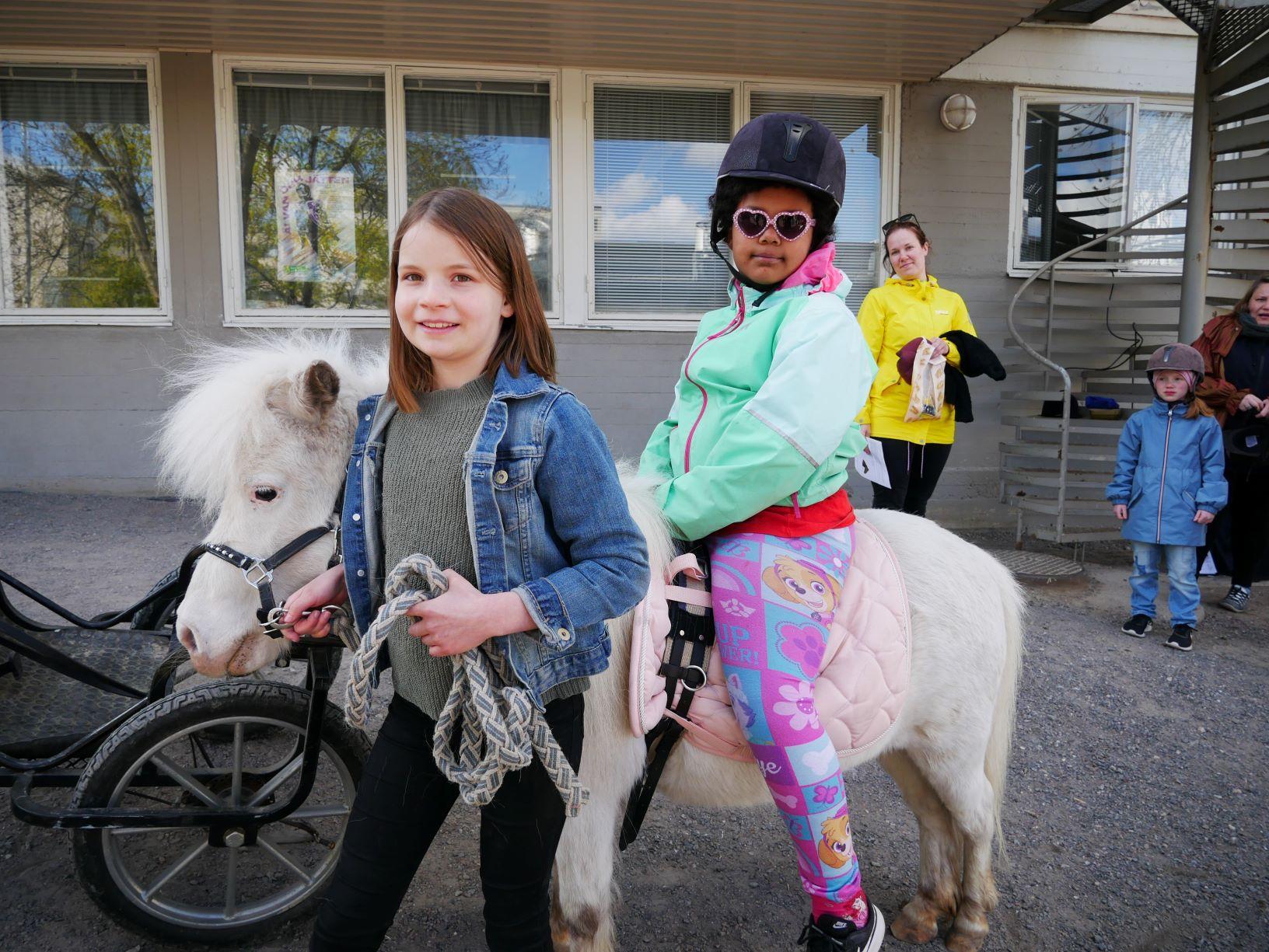 Flicka sitter på ponny