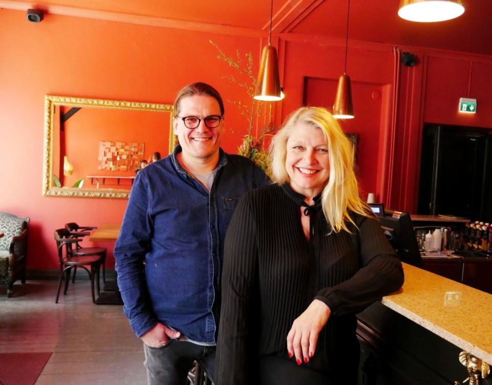 Två personer står vid bardisken i en bar med röda väggar
