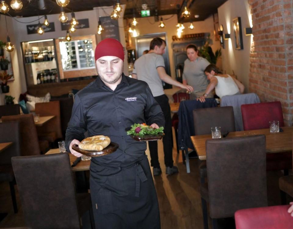 En person bär två portioner i en restaurang