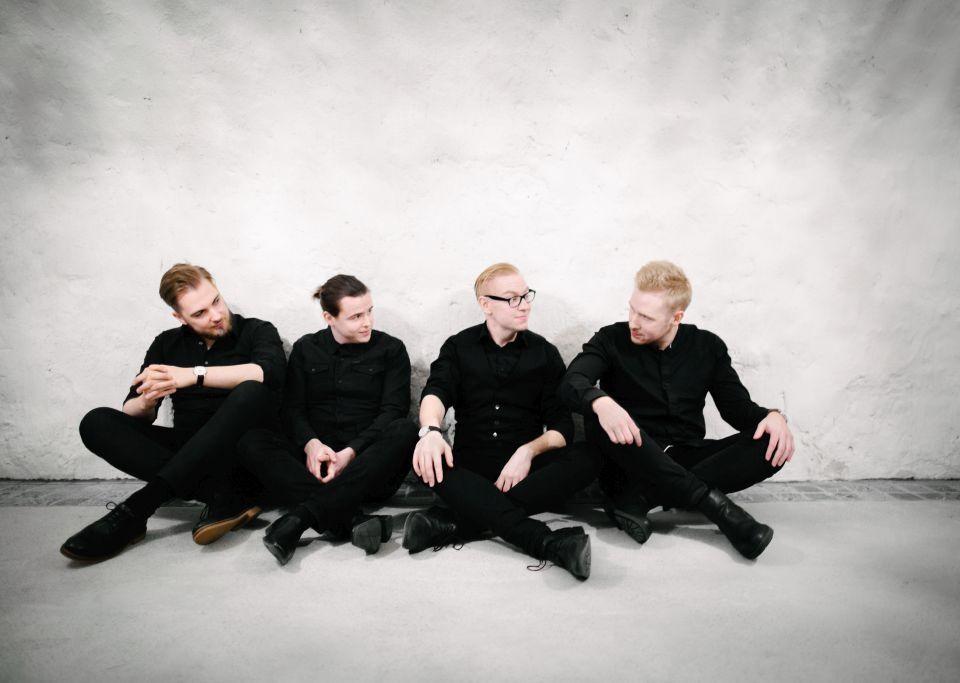 Fyra svartklädda män sitter på golvet mot en ljus bakgrund.