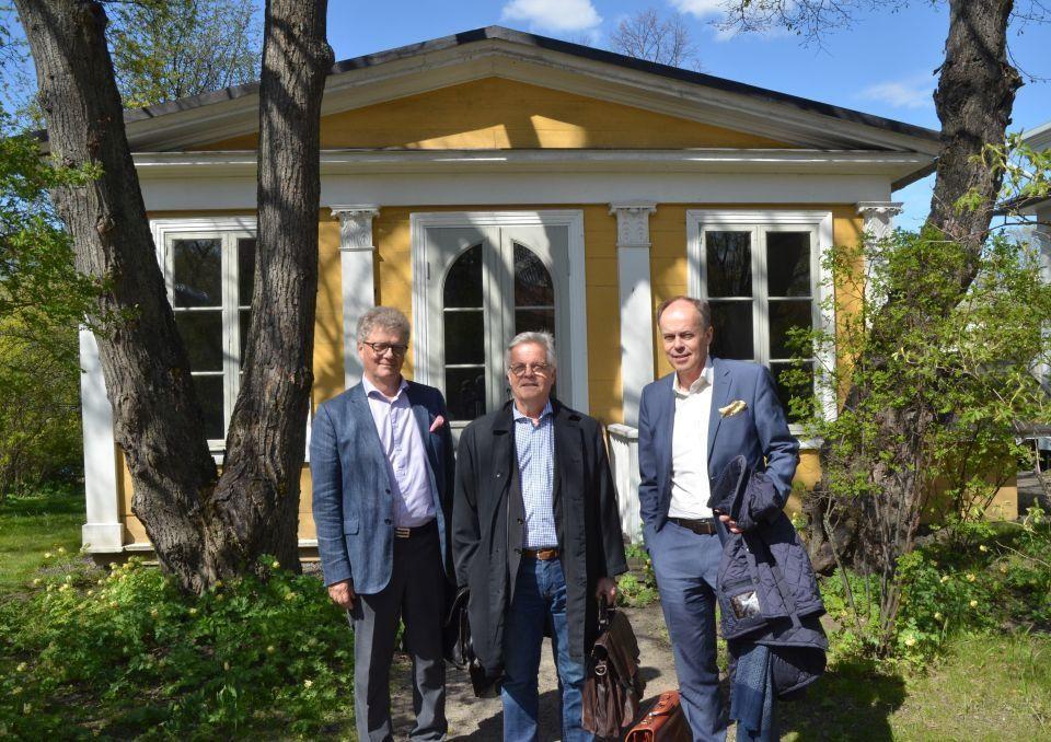 Tre män klädda i kostym står framför ett gult lusthus omringade av växtlighet.