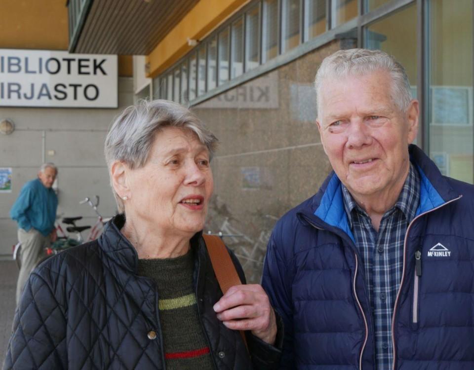 Äldre kvinna och man framför hus