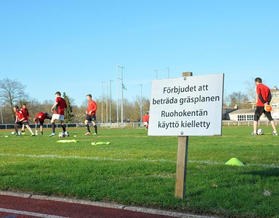 En fotbollsplan samt en skylt där det står att det är förbjudet att beträda gräsplanen