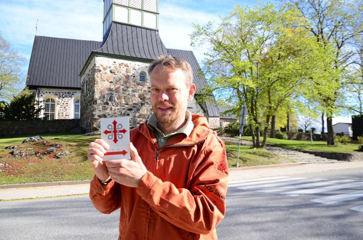 Man står framför Pargas kyrka och håller upp en skylt med pilgrimsmärke