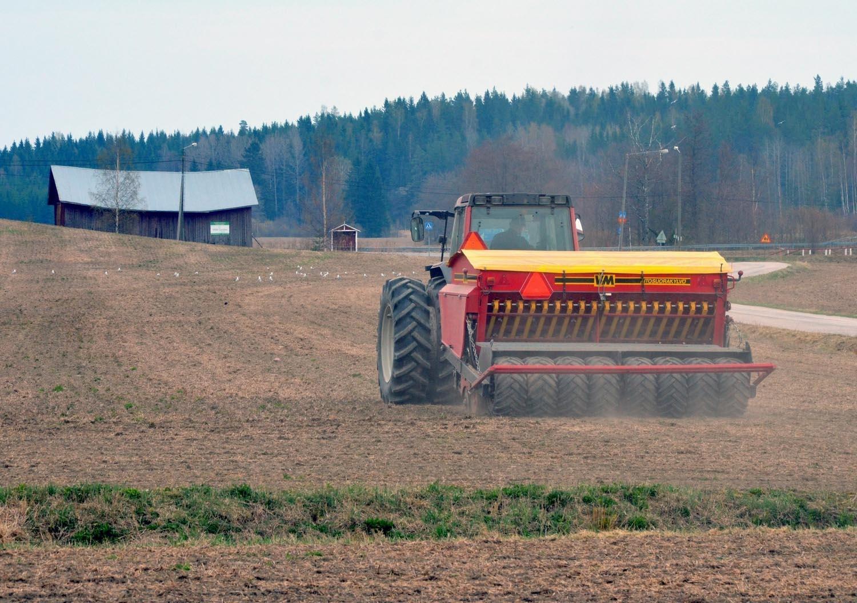 Traktor och såmaskin på åker